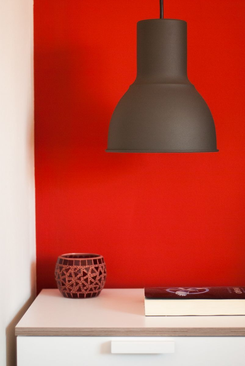 Mesilla de noche sobre pared roja