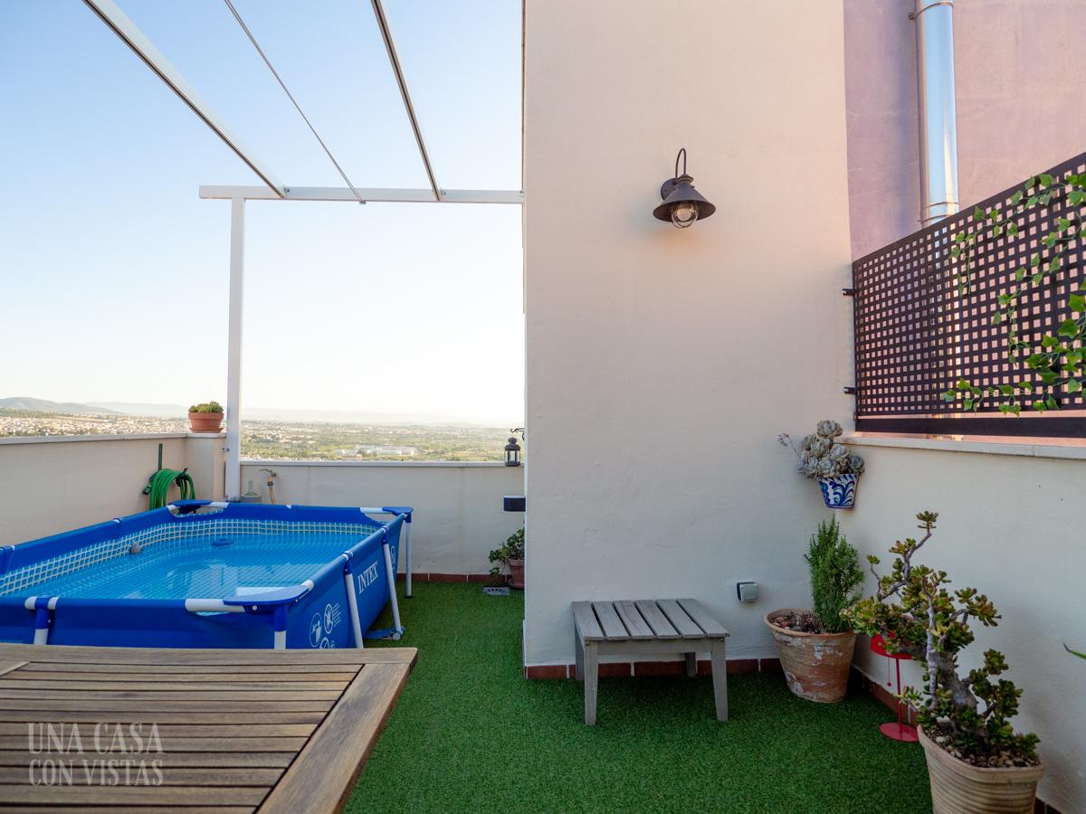 Terraza con piscina y césped artificial
